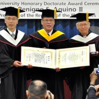 Philippine President Benigno S. Aquino III (center) holds his honorary doctorate diploma with Sophia University President Tadashi Takizawa (left) and Sophia School Corp. Chancellor Toshiaki Koso after receiving it at a ceremony at the university's Yotsuya Campus in Tokyo on Friday. | YOSHIAKI MIURA