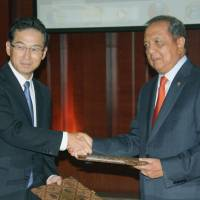Separate ways: Yoshihiko Okamoto, president of Nippon Asahan Aluminum (left), and Indonesian Industry Minister Mohamad Suleman Hidayat sign an agreement in Jakarta Monday to terminate a contract to run a joint aluminum production company in Indonesia. | KYODO