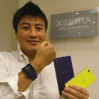 A piece of the pie: Kichiro Kurozumi shows off Sony Mobile Communications Inc.'s Xperia handsets and smartwatch at the firm's headquarters in October. | KAZUAKI NAGATA