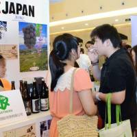 Taste test: Visitors at a food fair in Shanghai try out Japanese wine in June. | KYODO