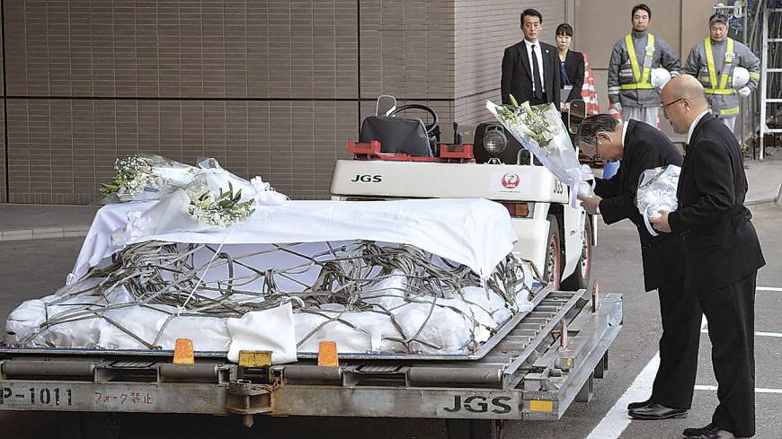 Unprecedented: JGC Corp. President Koichi Kawana (right) prepares to lay flowers on the coffin of a company official killed during January's Algerian hostage crisis.