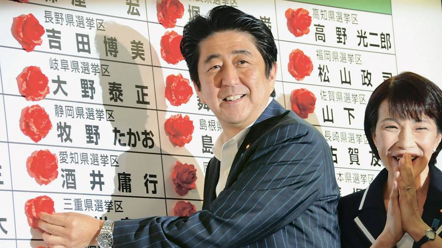 Smell of success: Prime Minister Shinzo Abe places rosettes next to the names of Liberal Democratic Party candidates who won seats in the July 21 Upper House election.