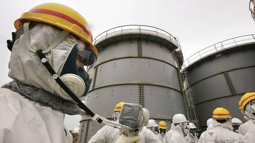 Hot water: A Tokyo Electric Power Co. employee measures radiation levels as journalists stand in front of storage tanks holding radioactive water at the Fukushima No. 1 plant on Nov. 7.