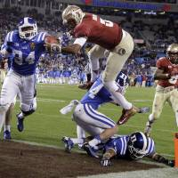 Heir apparent: Florida State's Jameis Winston (5) leaps over Duke's Bryon Fields (14) for a touchdown during the ACC Championship game on Dec. 7 in Charlotte, North Carolina. | AP