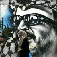Second opinion: A woman walks past graffiti of late Palestinian leader Yasser Arafat in the Palestinian refugee camp of Ain el-Helweh, in southern Lebanon, on Tuesday. French experts have ruled out a theory that Arafat was killed by poisoning, a source close to the investigation into the Palestinian leader's 2004 death said. | AFP-JIJI
