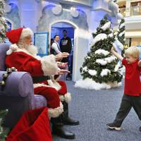 John Doris, 4, stretches out his arms to hug Santa Claus at the Ice Palace inside Cherry Creek Mall in Denver on Friday. | AP