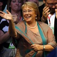 Back in: Presidential candidate Michelle Bachelet waves during a victory rally in Santiago on Sunday. | AP