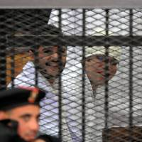 Egyptian example: Egyptian activists Ahmed Douma (left) and Ahmed Maher (right), two of the founders of the April 6 youth movement, which led the revolt against President Hosni Mubarak, stand in the dock during their trial on Sunday in Cairo. | AFP-JIJI