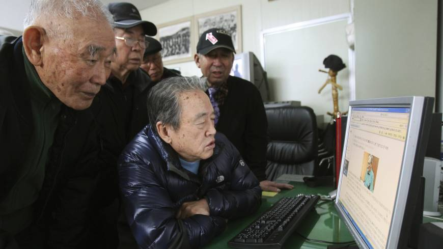Feared fighters: Park Young (center), a former member of the Kuwol partisan unit, and his comrades look at a website reporting on Merrill Newman, an elderly American tourist detained in North Korea, at the Kuwol partisan unit association office in Seoul on Monday.  Six decades before he went to North Korea as a curious tourist, Newman supervised the group of South Korean guerrillas during the Korean War who were perhaps the most hated and feared fighters in the North, former members of the group said.