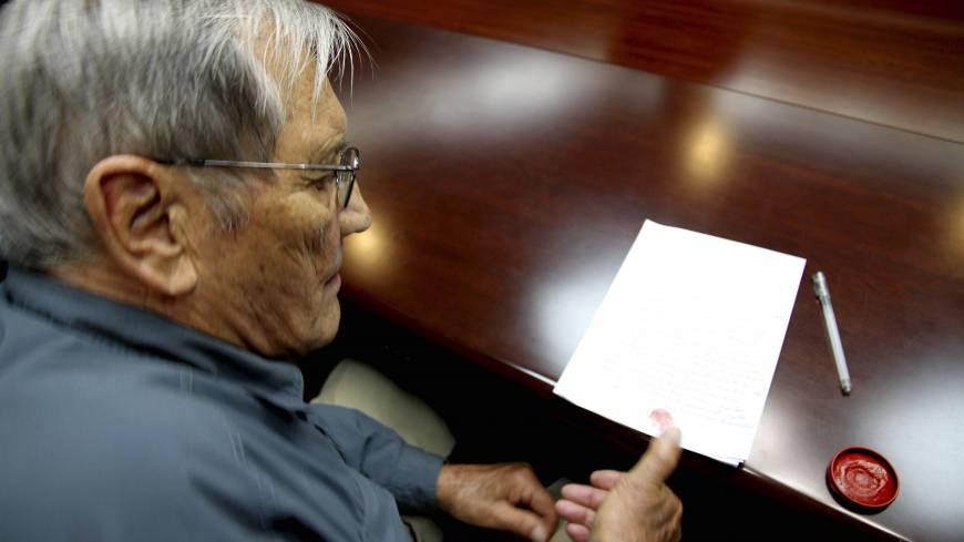War of words: U.S. citizen Merrill Newman, 85, applies his thumb print to a document that North Korean authorities say was an apology Newman wrote and read in North Korea on Nov. 9.