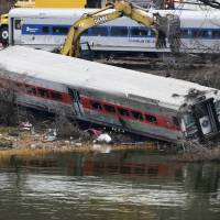 Accident waiting to happen?: A backhoe clears soil next to a derailed Metro-North train car on Monday in the Bronx borough of New York.  | AP