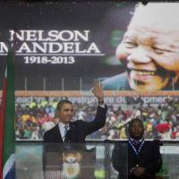 Potent voice: President Barack Obama waves as he arrives at the memorial service for former South African President Nelson Mandela at the FNB Stadium in the Johannesburg township of Soweto on Tuesday. World leaders, celebrities and citizens from all walks of life gathered on Tuesday to pay their respects to the anti-apartheid icon. | AP