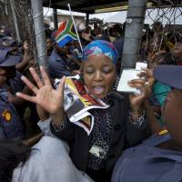 Crowd control: Women and children are allowed out from a waiting area behind a fence Wednesday after police became concerned they would get crushed by the crowd of mourners waiting and pushing forward to get on the buses that would transport them to Union Buildings to view the casket of Nelson Mandela lying in state in Pretoria. | AP
