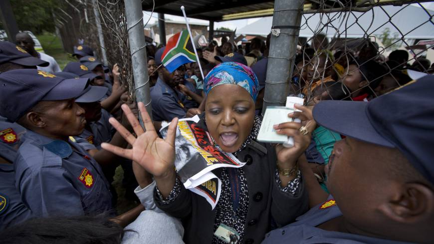 Crowd control: Women and children are allowed out from a waiting area behind a fence Wednesday after police became concerned they would get crushed by the crowd of mourners waiting and pushing forward to get on the buses that would transport them to Union Buildings to view the casket of Nelson Mandela lying in state in Pretoria.