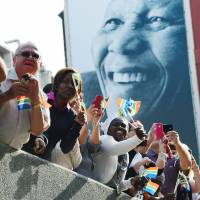 Fallen king: South Africans watch the funeral cortege carrying the body of former President Nelson Mandela to Union Buildings on Madiba Street in Pretoria on Wednesday. | AFP-JIJI
