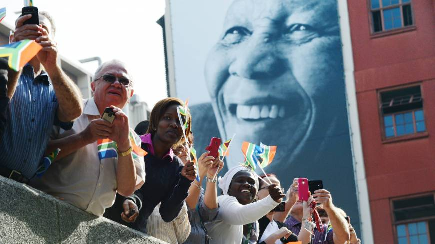 Fallen king: South Africans watch the funeral cortege carrying the body of former President Nelson Mandela to Union Buildings on Madiba Street in Pretoria on Wednesday.