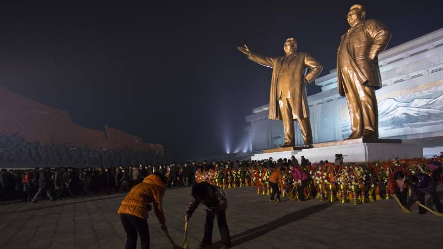 Sprucing up: As North Koreans arrive to pay their respects, women clean around the base of statues of late leaders Kim Il Sung (left) and Kim Jong Il in Pyongyang on Monday, the eve of the second anniversary of the death of Kim Jong Il.