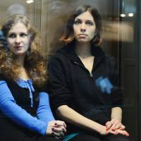 Token freedom?: Two jailed members of the all-girl punk band Pussy Riot, Maria Alyokhina (left) and Nadezhda Tolokonnikova, sit in a glass-walled cage during their trial in Moscow on Oct. 10, 2012. | AFP-JIJI