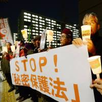 Fighting the law: Demonstrators hold candles and signs at the Diet on Monday during a protest against the state secrets bill being deliberated in the Upper House. | KYODO