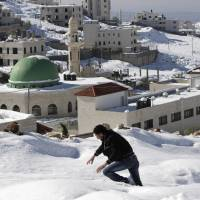 Uphill slog: A Palestinian walks through snow to his home in the West Bank city of Nablus on Sunday. | AP