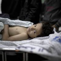 Retaliation: A Palestinian boy lies on a hospital trolley in Deir al-Balah, the Gaza Strip, after a series of Israeli air and tank strikes Tuesday killed his 3-year-old sister and wounded at least six other people. | AFP-JIJI