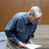 New orders: U.S. citizen Merrill Newman reads out a written apology for his alleged crimes both as a tourist and a combatant in the Korean War during his detention in Pyongyang on Nov. 9. North Korea said it deported Newman, 85, on Saturday. | AFP-JIJI