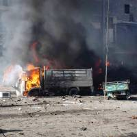 Indiscriminate killing: In this image provided by the Aleppo Media Center, vehicles burn after regime aircraft pummeled an opposition neighborhood in Syria's northern city of Aleppo on Sunday, killing scores of people. | AP