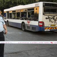 Ominous: An Israeli police officer stands at the scene of an explosion inside a bus on Sunday in the Mediterranean coastal city of Bat Yam, in the suburb of Tel Aviv. | AFP-JIJI