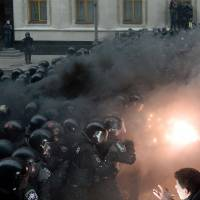 Fired up: A Ukrainian protester points a flare at riot police during clashes outside the president's office in Kiev on Sunday. | AFP-JIJI