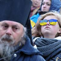 Eye-catching: A girl wearing glasses reading 'Power closes my eyes. I am not a slave' takes part in a march in the western Ukrainian city of Lviv on Monday. | AFP-JIJI