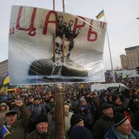 No confidence: Protesters hold a placard with a portrait of President Viktor Yanukovych and the word 'Czar' written across it during a rally in Kiev on Tuesday. | AP