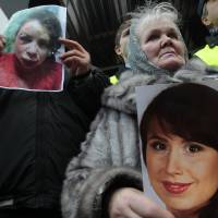Reprisal: Activists hold the photos of journalist and activist Tetyana Chernovil as they rally outside the Ukrainian Interior Ministry in Kiev on Wednesday. Chernovil was brutally beaten after publishing a story on the lavish suburban residence that she said belongs to the interior minister. | AP