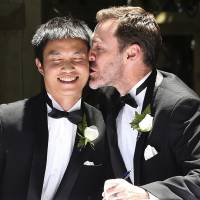 Stolen kiss: Ivan Hinton (right) and Chris Teoh celebrate after taking their wedding vows in Canberra on Saturday. | AP