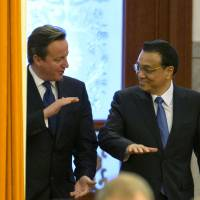 Bosom buddies: British Prime Minister David Cameron (left) chats with Chinese Premier Li Keqiang as they arrive for a welcome ceremony at the Great Hall of the People in Beijing on Monday. | AP
