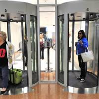 Traveling light: Passengers walk through security portals at the New Jersey's Atlantic City International Airport in November 2012. The Transportation Security Administration says that passengers left behind a record $531,395.22 in loose change at security checkpoints in 2012.   AP