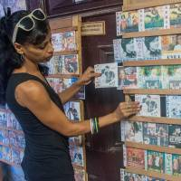 Escape from reality: A Cuban buys a South Korean soap opera DVD in Havana, on Dec. 5. After a reign of three decades, Brazilian soaps have found in South Korean's 'doramas' a strong rival in Cuba. | AFP-JIJI