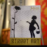 Cover girl: Street artist Banksy's 'Flower Girl' is shown on the cover of Julien's Auctions catalogue at the auction house in Beverly Hills, California, on Wednesday. | AFP-JIJI