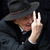 Mr. Bigg: Ronnie Biggs gestures on March 20 to waiting photographers as he arrives to attend the funeral of Bruce Reynolds, the mastermind of the 1963 Great Train Robbery, at Priory Church of Saint Bartholomew the Great in central London. Reports out of England on Wednesday said Biggs has died at age 84. | AFP-JIJI