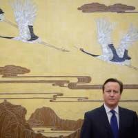 Watch the birdie: British Prime Minister David Cameron stands before a painting during a ceremony at the Great Hall of the People in Beijing on Monday. | AFP-JIJI