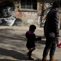 Sibling in the offing?: A woman and her child walk by a mural in Beijing on Nov. 17. China on Saturday formally allowed couples to have a second child if one parent is an only child, in the first major easing of its birth policy in three decades. | AP