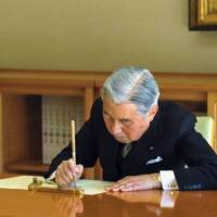It's official: Emperor Akihito signs a government document Nov. 8 at the Imperial Palace. | IMPERIAL HOUSEHOLD AGENCY/KYODO