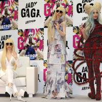 Pop art: Singer Lady Gaga poses for photographers with her life-size dolls during a news conference Sunday in Tokyo to promote her album 'Artpop.' | AP