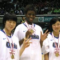 The champions: Oka Gakuen players (from left) Ai Yamada, Evelyn Mawuli and Sara Sakai proudly display their first-place medals after a 79-69 triumph over Gifu Girls in the All-Japan High School Tournament final on Saturday at Tokyo Metropolitan Gymnasium. | KAZ NAGATSUKA