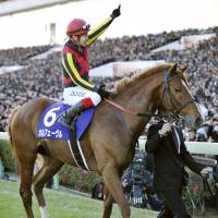 Fitting finish: Jockey Kenichi Ikezoe salutes the crowd after Orfevre's dominating performance in the Arima Kinen on Sunday. The two-time Prix de l'Arc de Triomphe runnerup closed out his career with a triumph. | KYODO