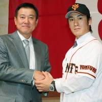 Join the club: New Yomiuri Giants signing Yasuyuki Kataoka (right) shakes hands with manager Tatsunori Hara on Monday. | KYODO