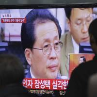 In focus: People watch a TV news report on North Korean leader Kim Jong Un's uncle, Jang Song Thaek, at Seoul Railway Station on Tuesday. | AP