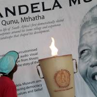 Larger than life: A boy looks up toward a portrait of late South African leader Nelson Mandela, at the Nelson Mandela Museum in Qunu, South Africa, on Saturday. | AP