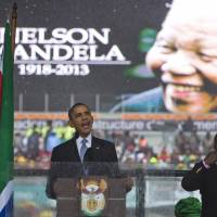 Misread?: President Barack Obama delivers his speech next to a sign language interpreter during a memorial service at FNB Stadium in honor of Nelson Mandela on Tuesday in Johannesburg. The national director of the Deaf Federation of South Africa says the man who provided sign language interpretation on stage was a fake. | AP