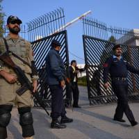 Treason trial: A paramilitary soldier and policemen stand guard outside a special court setup to try former Pakistani military ruler Pervez Musharraf in Islamabad on Tuesday. | AFP-JIJI