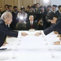 Looking for common ground: Okinawa Gov. Hirokazu Nakaima (left) hands a list of proposals to Prime Minister Shinzo Abe in Tokyo on Tuesday. | KYODO